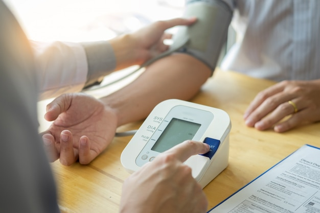 Doctor measuring and checking blood pressure of patient in hospital, health care concept.