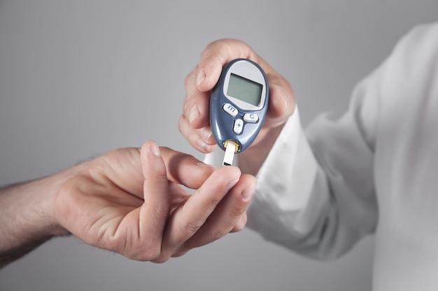 Врач измеряет уровень глюкозы у пациента.