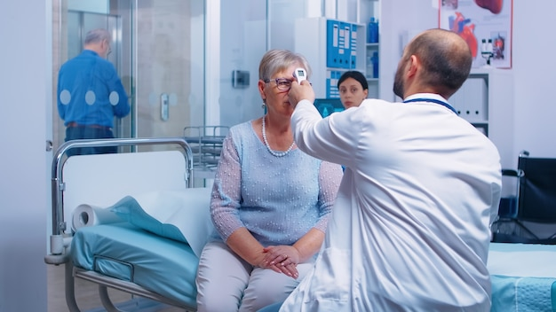 Врач, измеряющий температуру пожилой пожилой женщины с цифровым инфракрасным бесконтактным термометром в современной частной клинике. пациент сидит на больничной койке, болезнь системы здравоохранения и профилактика заболеваний