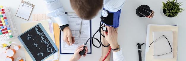 환자 어깨 평면도 동맥 고혈압 치료 개념에 압력을 측정하는 의사