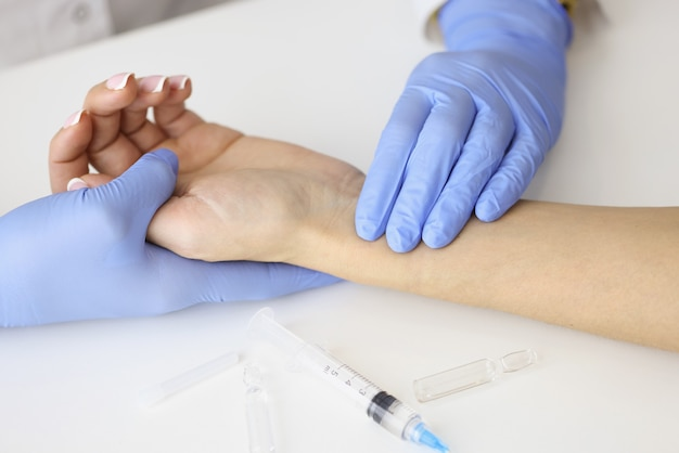 Doctor measuring pulse on patient forearm near empty syringe and medication closeup