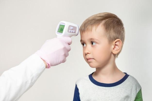 医師が温度を測定する赤外線少年と子供男の子