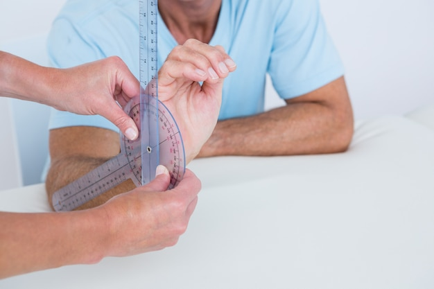 Doctor measuring wrist with goniometer