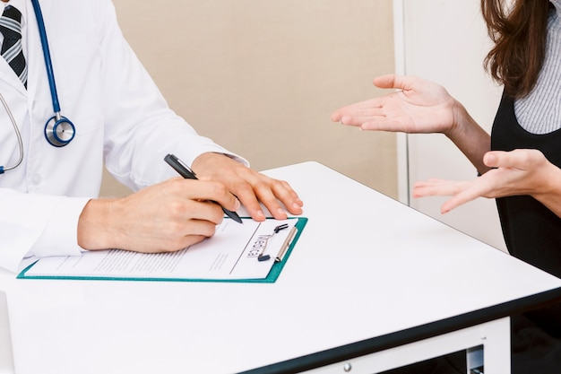 Doctor medical check up information with woman patient on doctors table in hospital