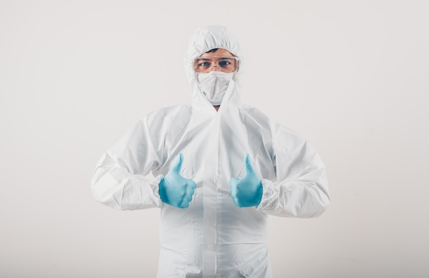 A doctor in medical gloves and protective suit showing thumbs up in light background . coronavirus