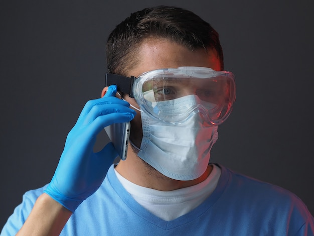 Doctor in medical gown face mask gloves and goggles on gray background, talking on the phone. epidemic pandemic coronavirus 2019-ncov, covid-19 virus.
