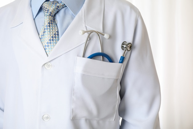 Doctor in medical gown with blue stethoscope, close up