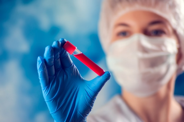 Doctor in medical mask and blue gloves holding tube with blood test. medicine and health care concept.