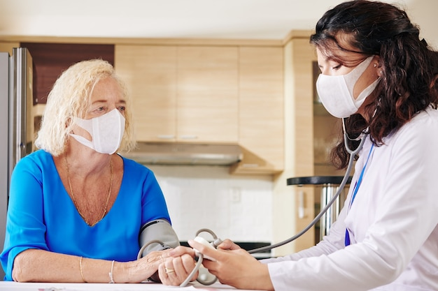 Doctor in medical mask checking blood pressure