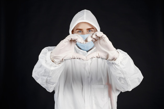 Doctor in a medical mask. coronavirus theme. isolated over black wall. woman in a protective suit.