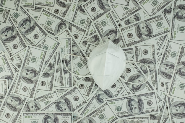 ウイルス保護とお金のためのドクターメディカルマスク100ドル紙幣のスタック多くの背景