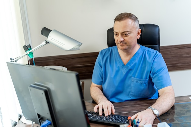 Doctor in medical office. medic sits at computer. man in scrubs.