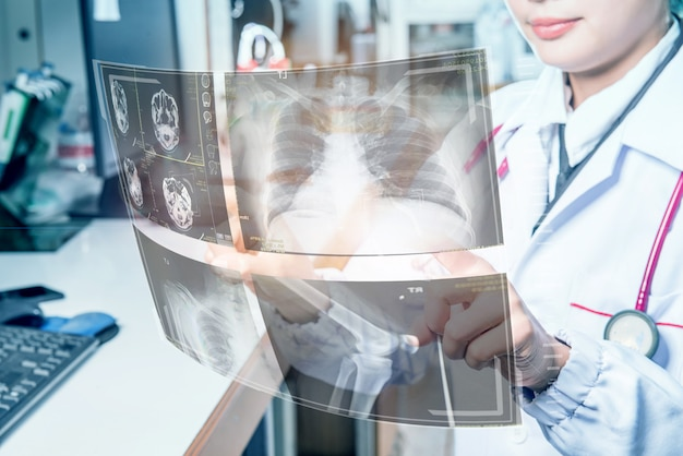Doctor medical operating futuristic medical interface with x-rays and digital screens.