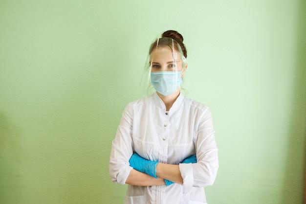 Врач, медицинский специалист, косметолог, стоматолог носит защитный экран, маску и резиновые перчатки. медицинская форма. зеленая стена фон. в помещении в клинике.