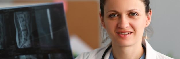 의사 신경과 의사는 클리닉 초상화에서 척추의 x 레이를 손에 보유하고 있습니다.