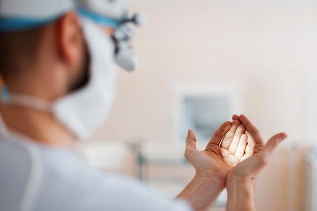 Врач нейрохирург в медицинской маске в профессиональных лупах светит на руках, проверяет бинокулярные лупы. подготовка к операции. вид сзади
