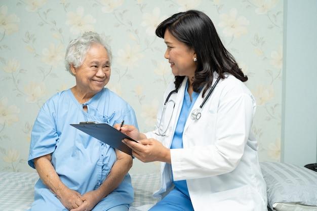 病院でアジアの年配の女性とクリップボードの医師のメモ