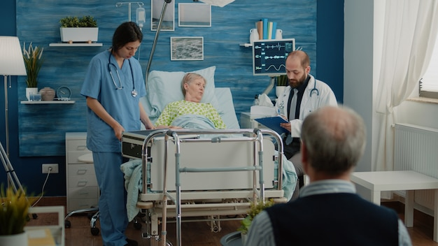 Doctor and nurse giving assistance to retired woman