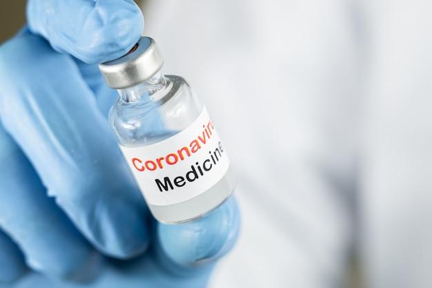 Doctor or nurse hand holding coronavirus injection medicine