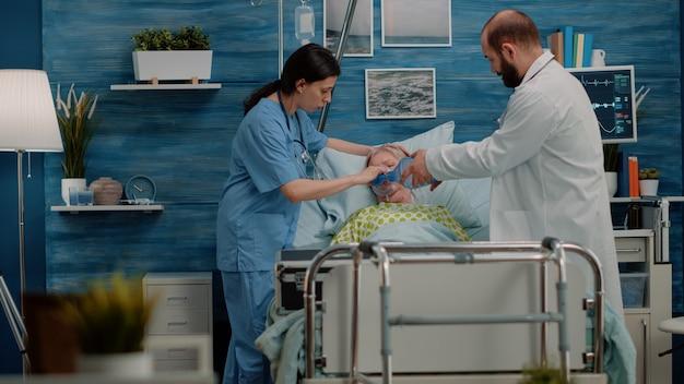 Doctor and nurse helping elder patient with disease in bed