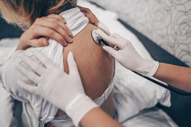 Врач медсестры в медицинских перчатках слушает дыхание с помощью стетоскопа, подозревающего коронавирус (covid-19). первые симптомы концепции. женщина болеет гриппом вирусной инфекции в домашнем изоляторе