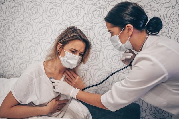 Врач медсестры в защитной маске слушает дыхание с помощью стетоскопа, подозревающего коронавирус (covid-19). первые симптомы концепции. женщина болеет гриппом вирусной инфекции в домашнем изоляторе