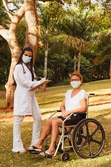 Doctor nurse making notes on clipboard consulting elderly woman in home garden