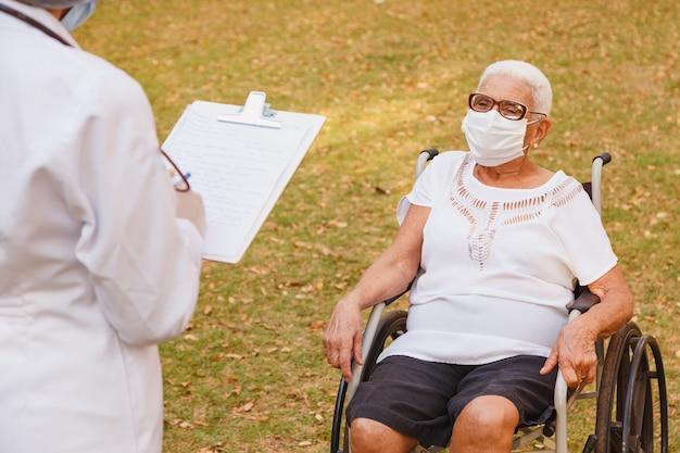 自宅の庭で年配の女性に相談するクリップボードにメモをとる医師の看護師