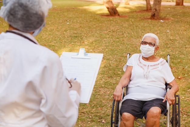 집 정원에서 노인 여성 컨설팅 클립 보드에 메모를 만드는 의사 간호사