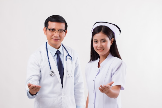 Doctor and nurse medical team pointing inviting hand at you