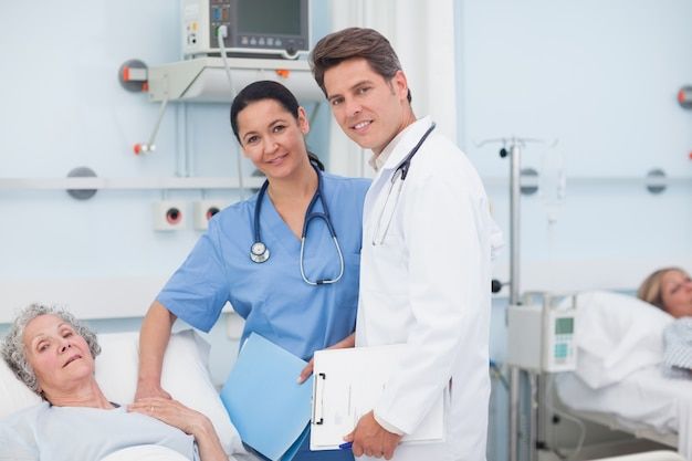 Doctor and nurse next to a patient