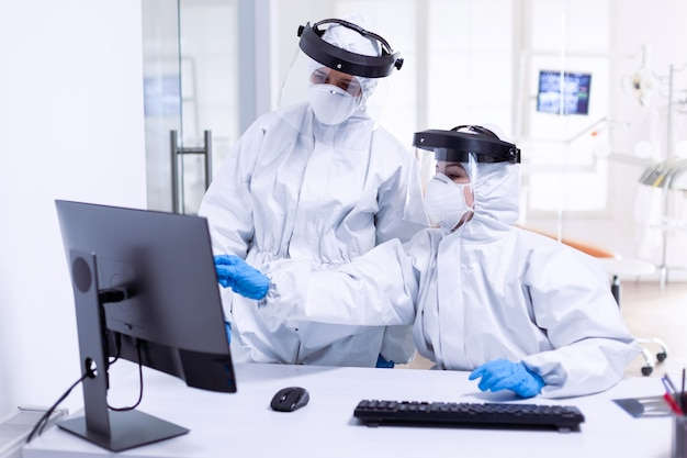 Doctor and nurse in ppe suit looking at monitor during global pandemic with covid-19. medicine team wearing protection gear against coronavirus pandemic in dental reception as safety precaution.