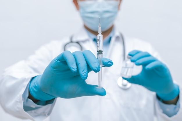 Doctor, nurse, scientist hand in blue gloves holding flu, measles, coronavirus, covid-19 vaccine disease preparing vaccination shot