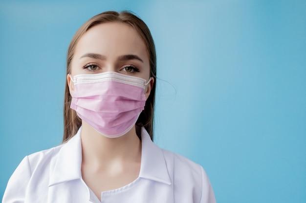 医師看護師が外科医のマスクの後ろに笑っています。青の背景に若い白人女性モデルのポートレート、クローズアップ。 covid-19を保護するためにマスを着ている女性