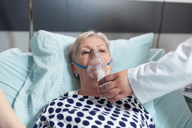 Doctor and nurse supervising senior woman breathing with oxygen mask