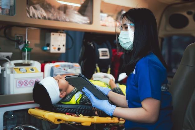 医師/看護師はタブレットを使用して、職場での事故で負傷した患者の情報を確認します。負傷者を救急車で病院に運びながら。労働災害で負傷した建設作業員