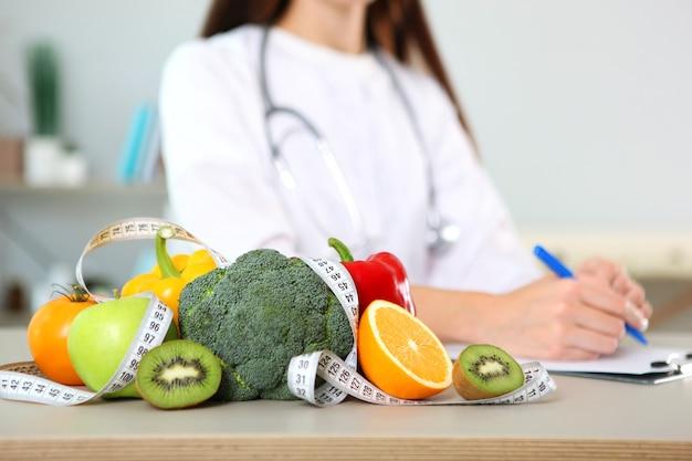 Врач-диетолог в своем кабинете демонстрирует концепцию здорового питания