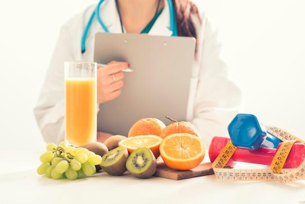 Врач диетолог в офисе со здоровыми фруктами