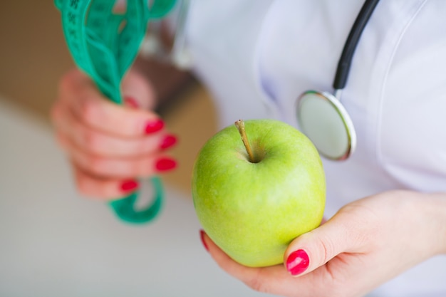Doctor nutritionist measuring green apple in her office.