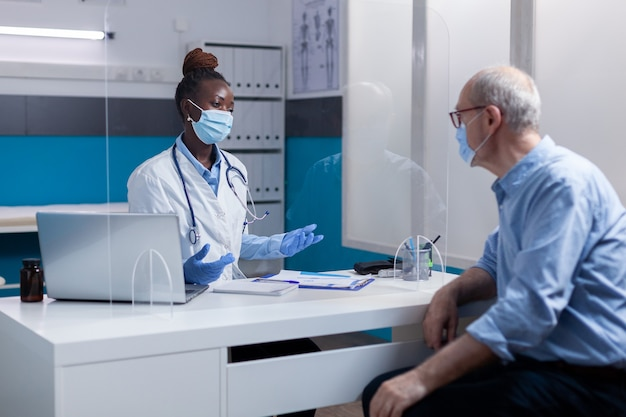 フェイスマスクを身に着けているアフリカ系アメリカ人の民族の医者
