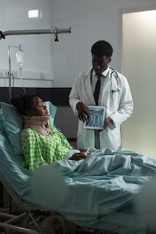 지원 및 건강 관리를 위해 자궁 경부 목 칼라가 있는 병원 병동 침대에 누워 있는 젊은 환자에게 x선 결과를 보여주는 아프리카 민족 의사. 태블릿을 보고 있는 남자와 아픈 여자