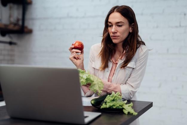 栄養学の医師はオンラインで相談します。女性栄養士がノートパソコンの前の机に座って、ライブビデオ通話で話します。