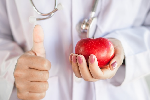 Doctor offering to eat healthy fruit red apple