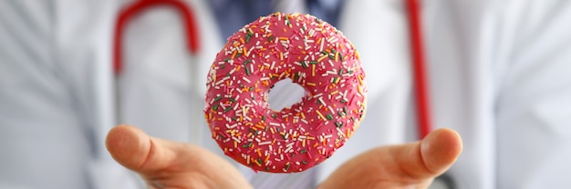 Doctor in office holding in hand pink doughnut closeup