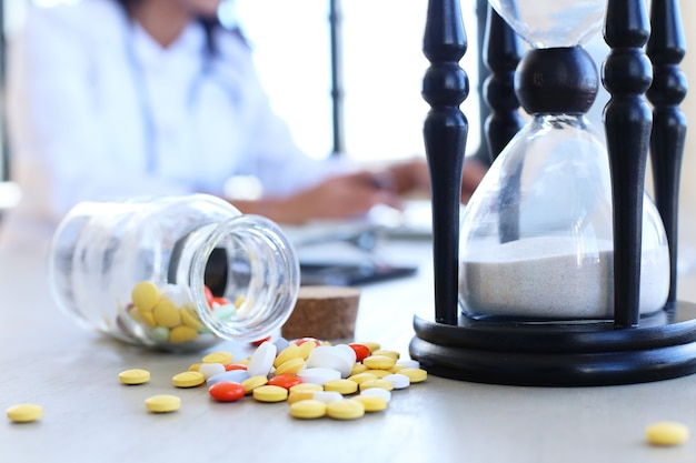 Doctor at the office with pills and hourglass