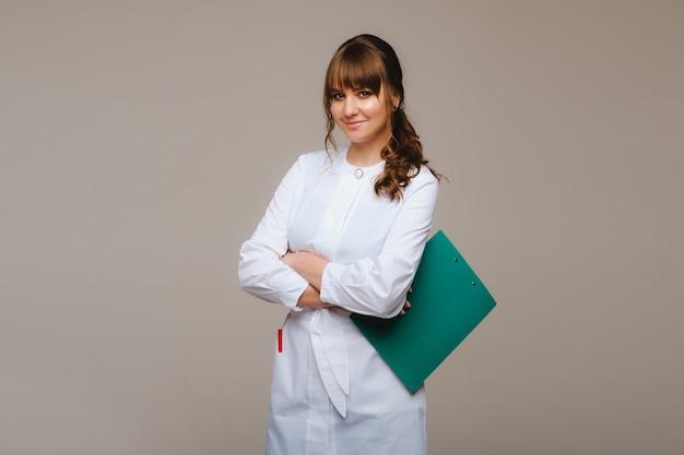 Врач на сером фоне с медицинским заключением в руках