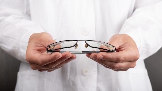 Врач офтальмолог держит очки, костыли для глаз.