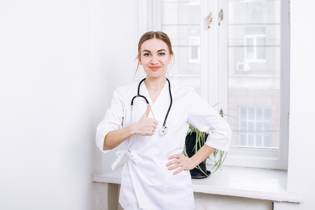窓の近くの白い壁に聴診器を備えた白い制服を着た医師または医療専門家は親指を表示します