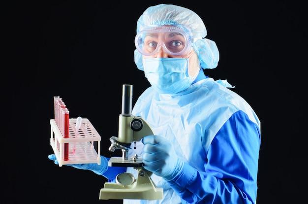 血液検査管と顕微鏡で血液サンプルを分析する医師または検査技師。