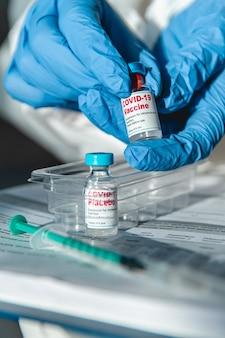 Covid 19 백신을 들고 보호 복을 입은 의사 또는 간호사